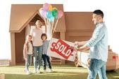 mladá rodina stěhování do nového domu cardbord izolované na bílém