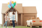 Photo little kid presenting balloons to girlfriend in front of cardboard house isolated on white