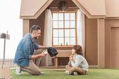 Fotografie otec učí svého syna, jak hrát baseball na trávě před kartónové house