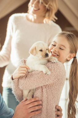 mother and happy little daughter playing with adorable labrador puppy