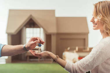 cropped shot of real estate agent passing key to happy woman in front of cardboard house