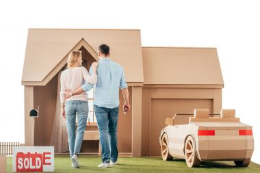 rear view of couple walking to their new cardboard house isolated on white