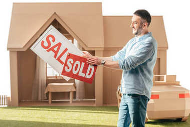 man holding sale and sold signboards in front of cardboard house isolated on white