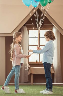 kid presenting balloons to beautiful little girlfriend in front of cardboard house