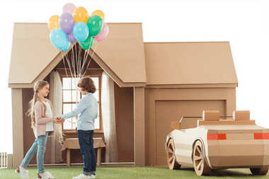 little kid presenting balloons to girlfriend in front of cardboard house isolated on white