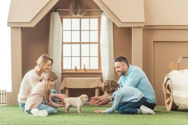 happy family with adorable puppy on yard of cardboard house