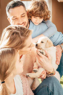 Happy young family with adorable labrador puppy