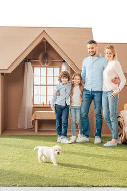 happy young family with adorable puppy on yard of cardboard house isolated on white