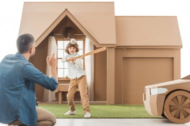 father teaching his son how to play baseball in front of cardboard house isolated on white