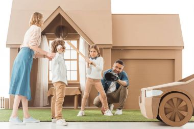 young family playing baseball together on yard of cardboard house isolated on white