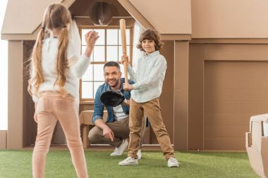 father teaching his kids how to play baseball in front of cardboard house