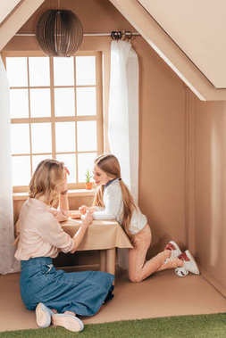 mother and adorable little daughter in cardboard house spending time together