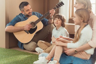 happy handsome father playing guitar for kids and wife at new cardboard house