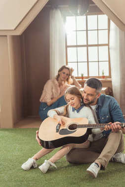 handsome father and daughter playing guitar on grass in front of cardboard house with mother sitting inside