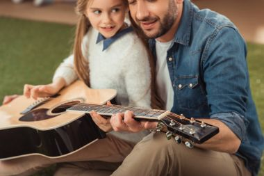 handsome father and daughter playing guitar while sitting on grass