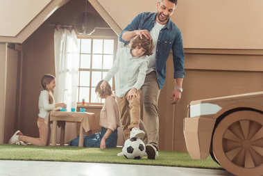 handsome father teaching his som to play soccer on yard of cardboard house