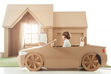 kid riding cardboard car in front of house while girlfriend waving to him isolated on white