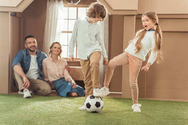 brother and sister playing football on yard of cardboard house while parents looking at them