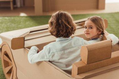 little kids riding cardboard car