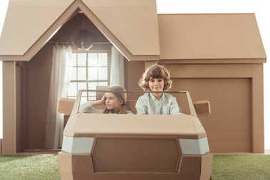 kids riding cardboard car in front of house