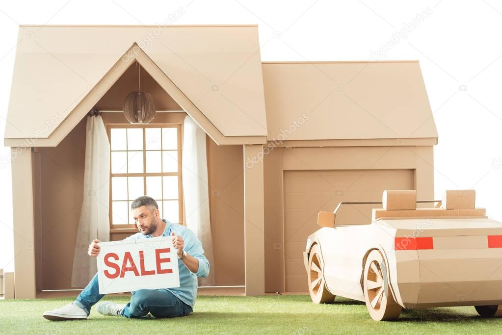 man holding sale signboard in front of cardboard house isolated on white