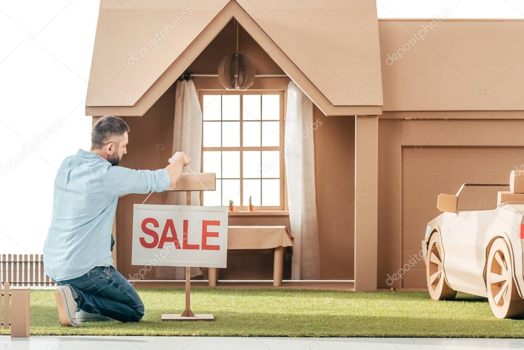 man hanging sale signboard in front of cardboard house isolated on white