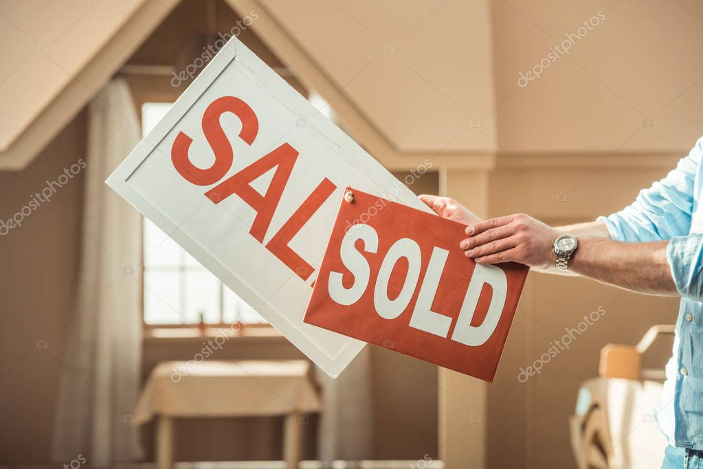 cropped shot of man holding sale and sold signboards in front of cardboard house
