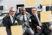 Fotografie multikulturní usmívající se podnikatelé při pohledu na poznámky během setkání v kanceláři