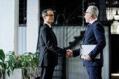 boční pohled na vysokých obchodních kolegů potřesení rukou