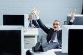 Selektivní fokus šťastný podnikatel sedí na pracovišti s nohama na stole