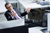 Veselá podnikatel v brýle sedí na pracovišti v úřadu