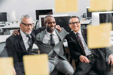 multicultural smiling businessmen looking at notes during meeting in office
