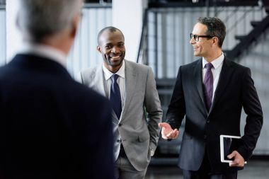 selective focus of smiling multiracial businessmen having conversation while walking in office
