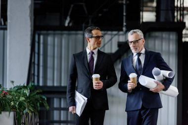 portrait of businessmen with coffee to go in hands walking in office