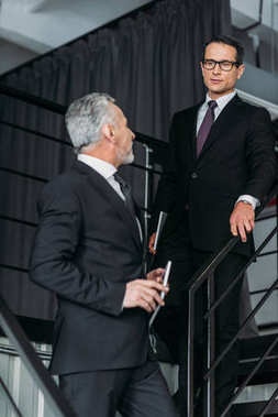 businessmen in suits having conversation while going down on steps in office