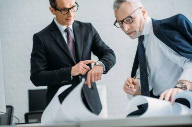 businessmen in suits and eyeglasses having meeting in office