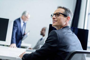 selective focus of smiling businessman in eyeglasses looking away in office