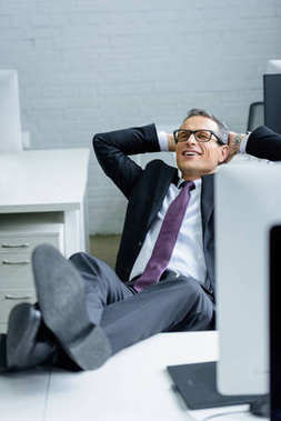smiling businessman with hands behind head resting at workplace