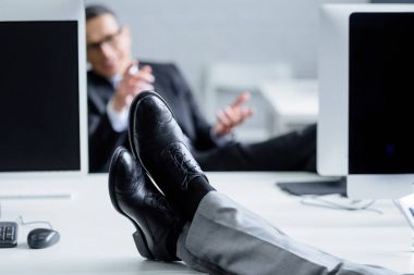partial view of businessman at workplace with legs on table