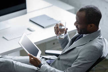 african american businessman with glass of water using tablet at workplace in office