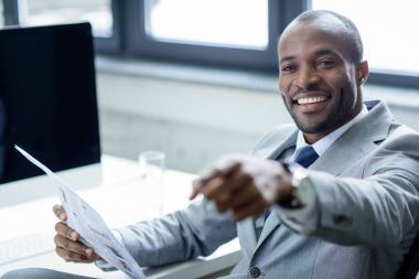 smiling african american businessman with newspaper pointing away at workplace