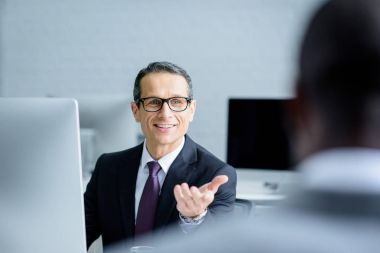 selective focus of smiling businessman talking to colleague while working in office