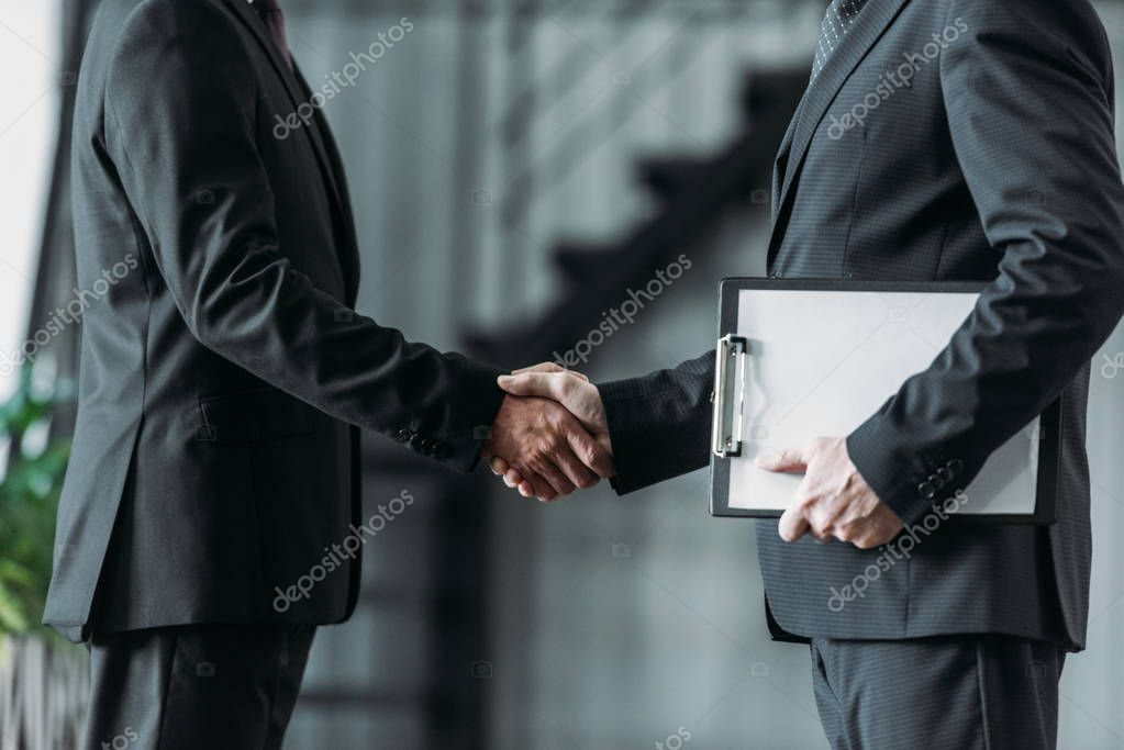 partial view of businessmen shaking hands