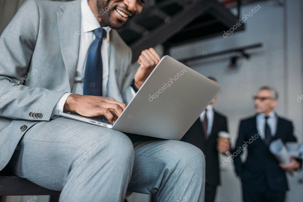 partial view of african american businessman working on laptop