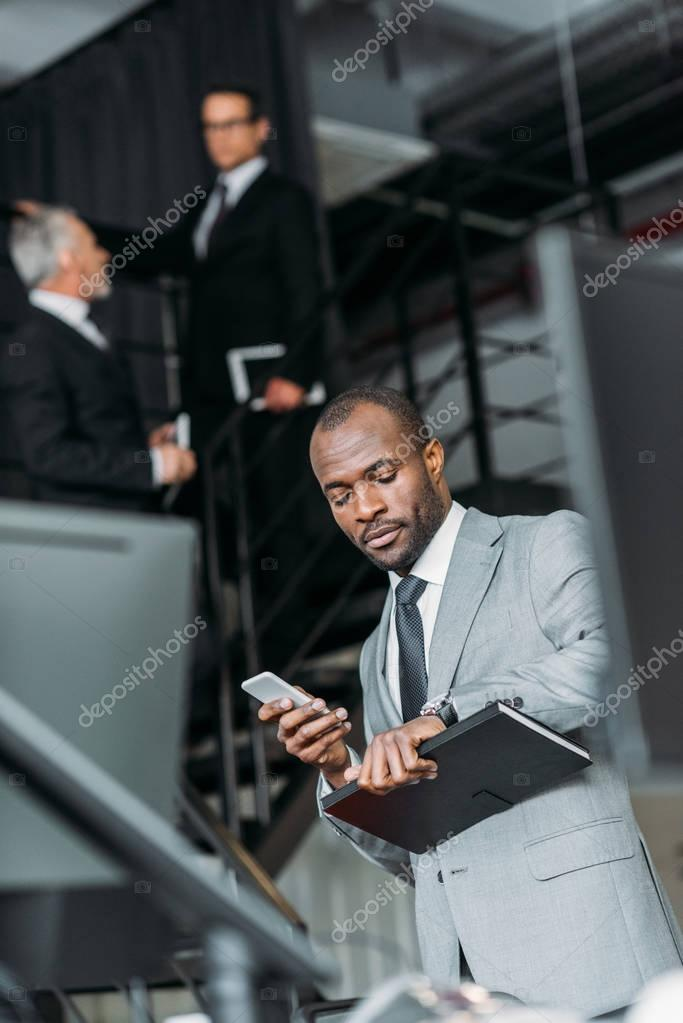 selective focus of african american businessman with smartphone checking time