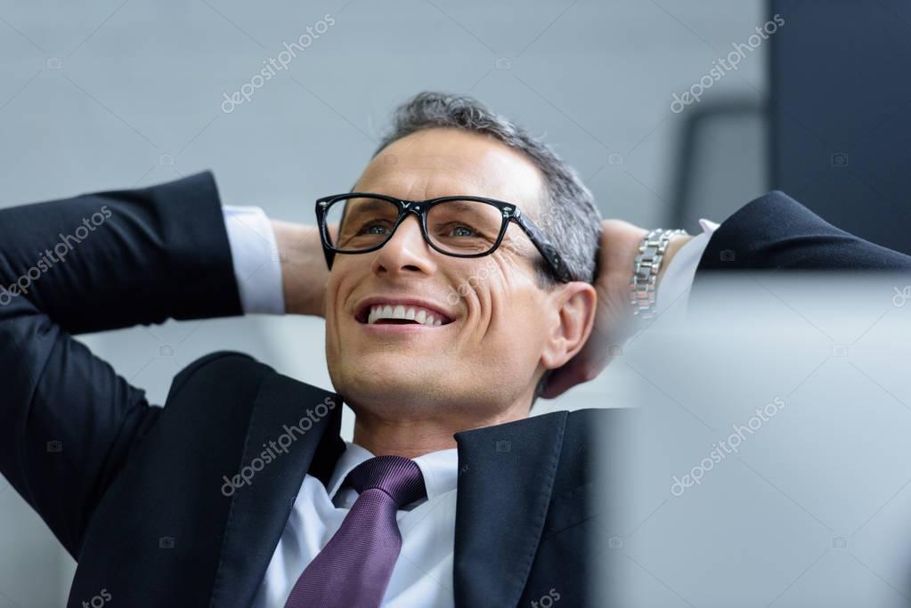 portrait of cheerful businessman in eyeglasses with hands behind head
