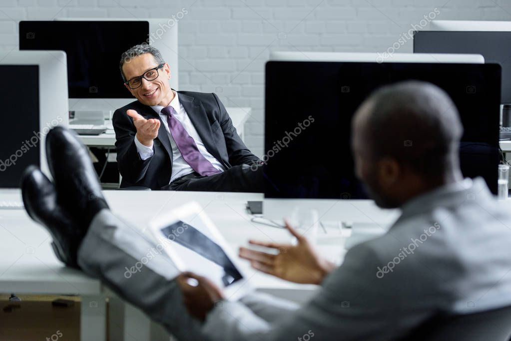 selective focus of multicultural businessmen having conversation at workplace in office