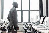 Afrikanisch-amerikanischer Geschäftsmann mit Tablet in der Hand im Büro