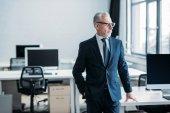 senior businessman in eyeglasses standing at workplace in office