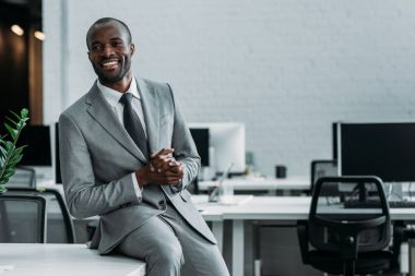 smiling african american businessman sitting on table in office